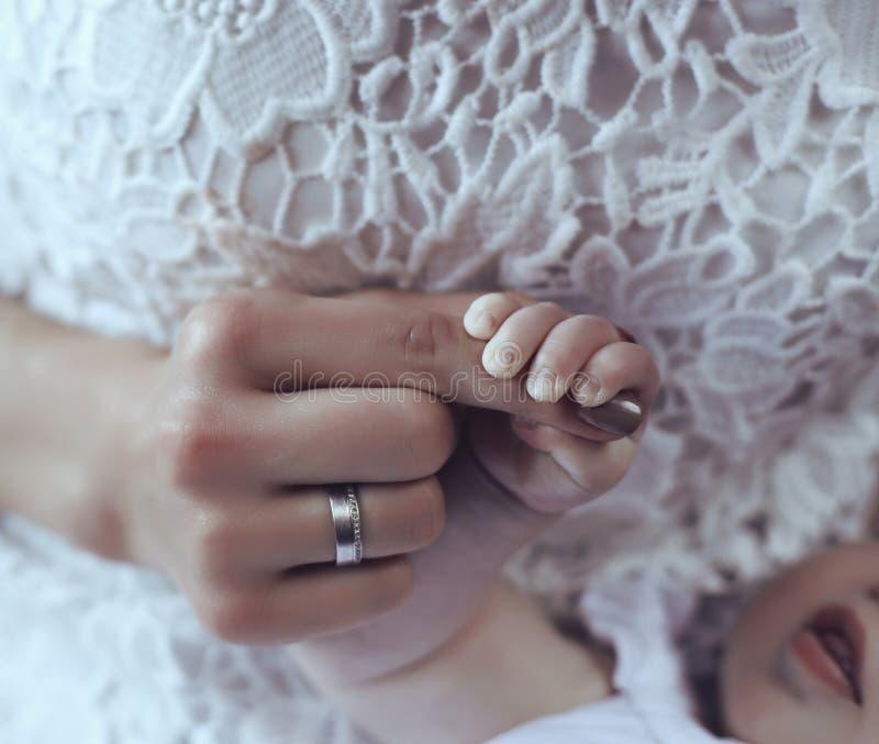 Foto dolce della mano sveglia del bambino in mani della mamma fotografia stock