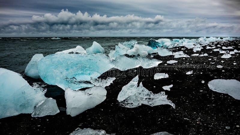 A foto dos iceberg moldou afastado na praia escura foto de stock