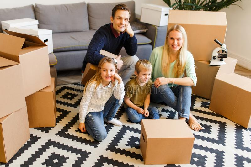 Foto dos pais com as crianças que sentam-se no assoalho entre as caixas de cartão t fotos de stock royalty free
