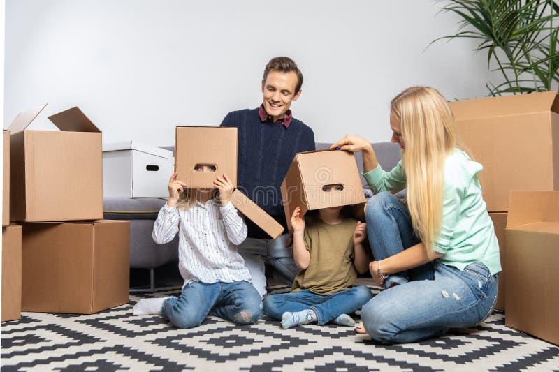 Foto dos pais e das crianças com as caixas de cartão em suas cabeças que sentam-se no apartamento novo foto de stock royalty free