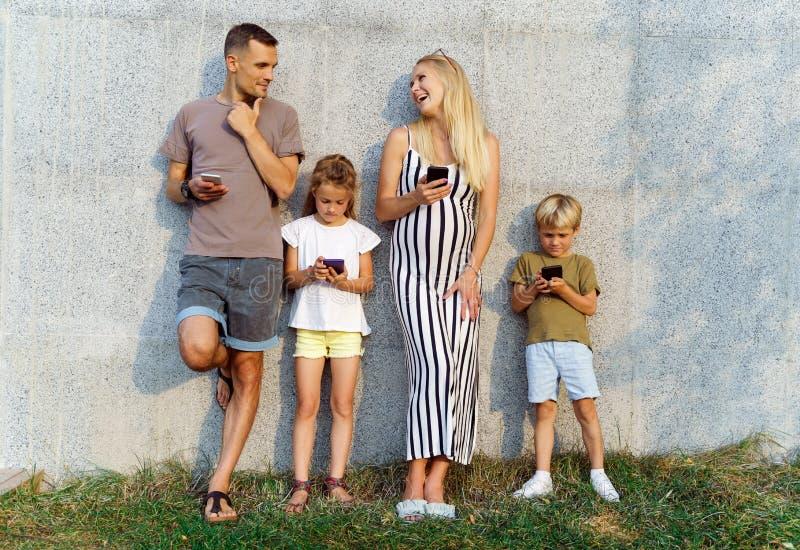 Foto dos pais e das crianças com os telefones em suas mãos que estão no muro de cimento na rua fotografia de stock