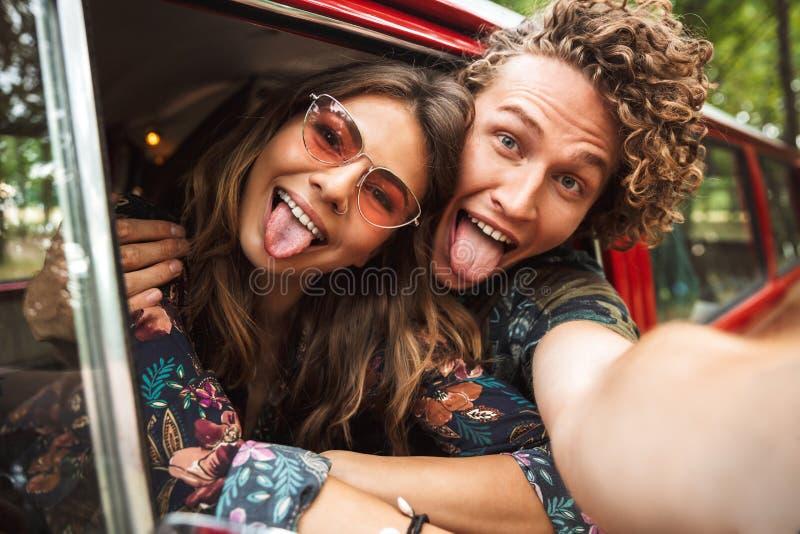 Foto dos pares de amor da hippie que sorriem, e mostrando o wh do sinal de paz foto de stock royalty free