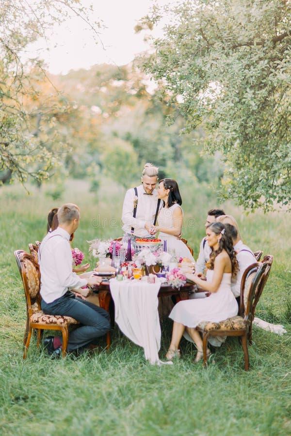 A foto dos recém-casados que cortam sua primeira parte de bolo de casamento junto, quando os convidados a olharem E foto de stock royalty free