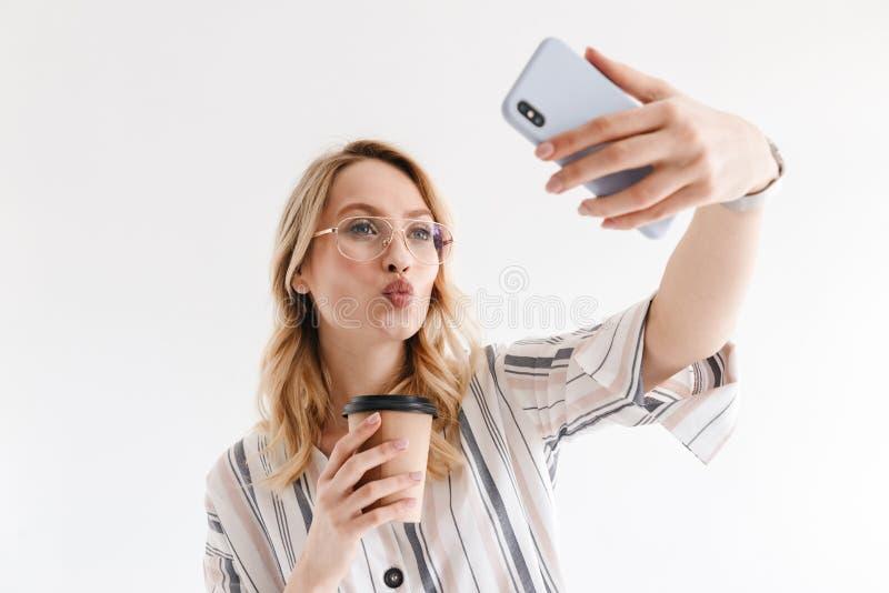Foto dos vidros vestindo da mulher loura bonita que tomam a foto do selfie no smartphone imagem de stock