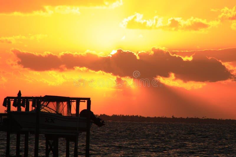 Foto dram?tica de la puesta del sol con la elevaci?n del barco en primero plano imagenes de archivo