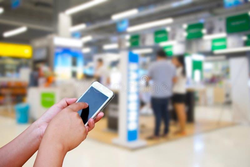 Foto e smartphone no shopping e povos borrados com BO imagens de stock royalty free