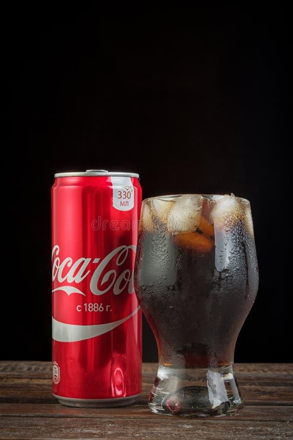 A foto editorial do vidro da coca-cola com gelo e pode na tabela de madeira com o espaço da cópia isolado no preto Foto vertical imagens de stock royalty free