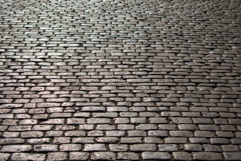 Foto einer alten Straße mit einer Steinbeschaffenheit überschwemmte mit Sonnenlicht bei Sonnenuntergang lizenzfreie stockfotos