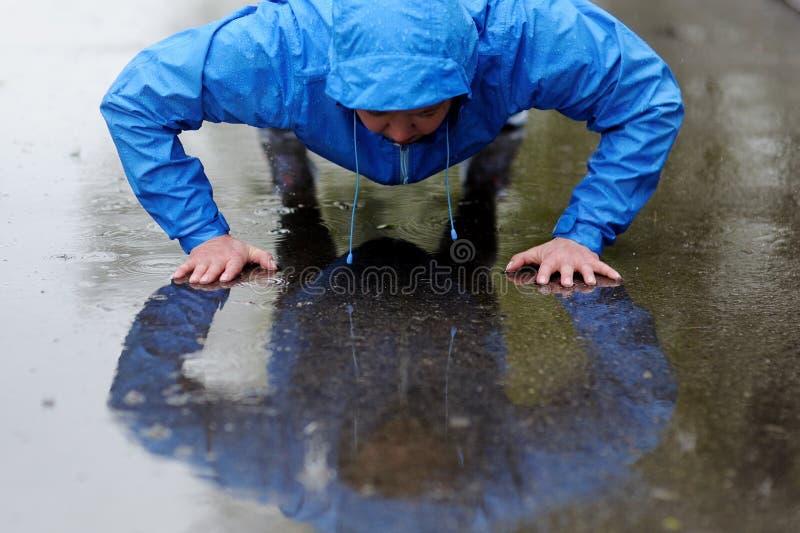 Foto einer jungen athletischen Frau, die im Regen trainiert lizenzfreies stockfoto