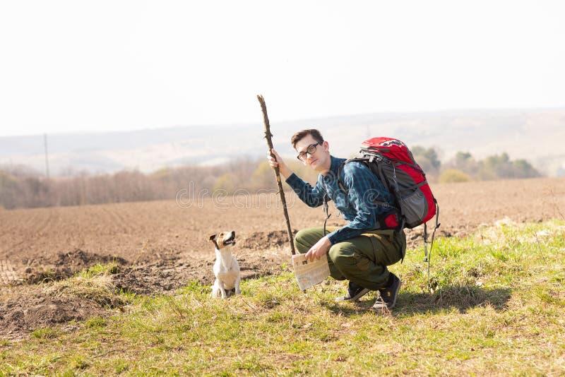 Foto eines jungen Touristen und seines Hundes, gehend in die Landschaft stockbild