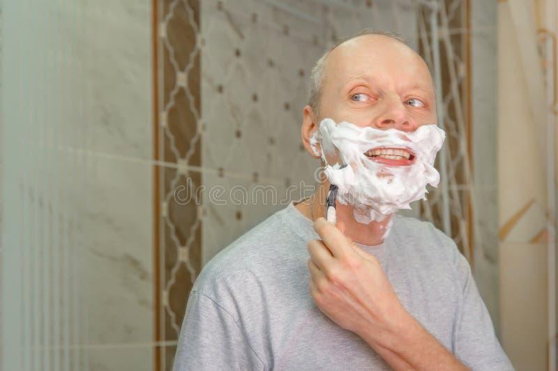 Foto eines Mannes, der sein Gesicht rasiert stockbilder