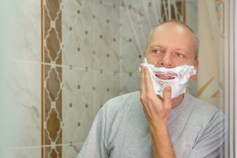 Foto eines Mannes, der sein Gesicht rasiert stockbild