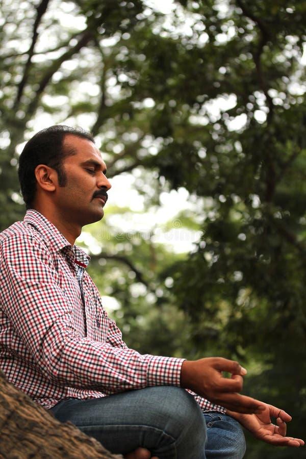 Foto eines stattlichen indischen meditierenden Geschäftsmannes stockfotografie