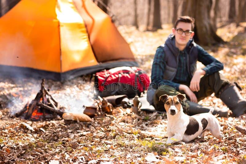 Foto eines Touristen mit einem Hund, stehend im Wald nahe dem Feuer und dem orange Zelt still lizenzfreie stockfotos