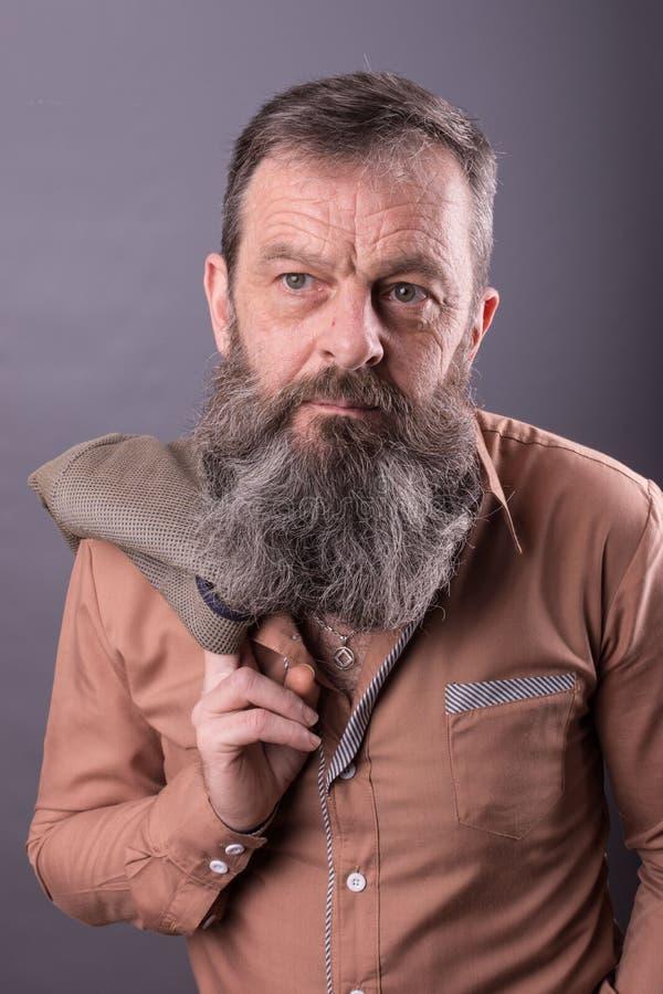 Foto eines verärgerten mürrischen alten Mannes, der sehr missfallen schaut Männlicher Mann mit langem Bart auf seinem Gesicht Sch lizenzfreie stockbilder