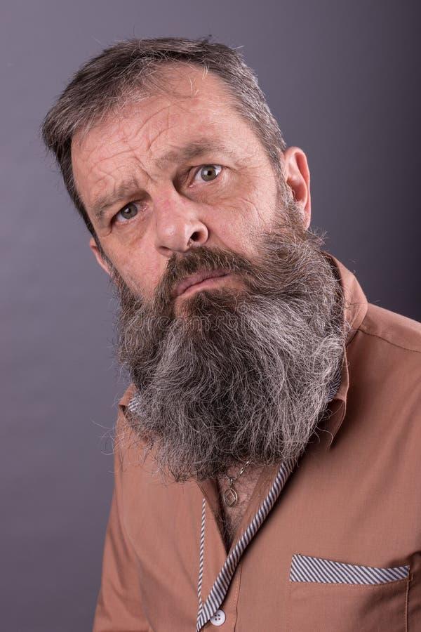 Foto eines verärgerten mürrischen alten Mannes, der sehr missfallen schaut Männlicher Mann mit langem Bart auf seinem Gesicht Sch stockfoto