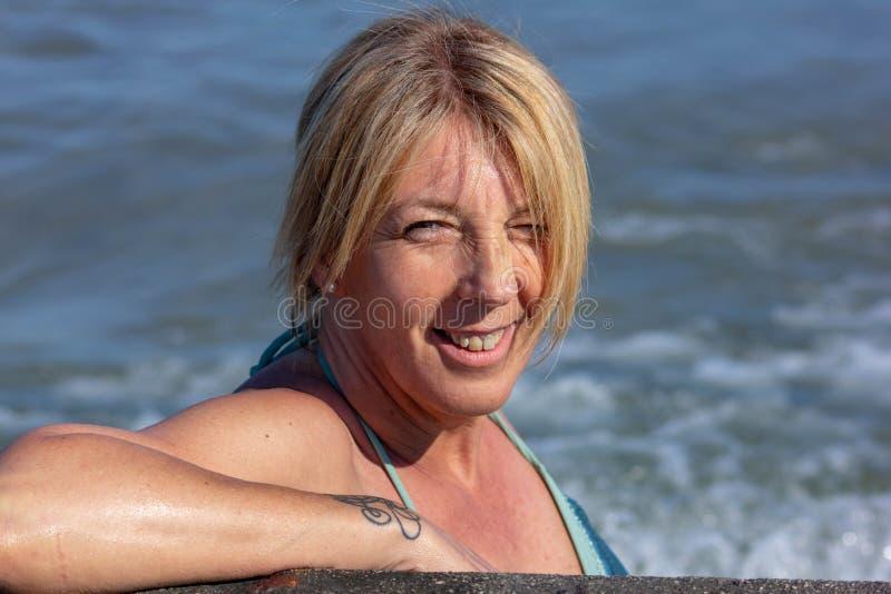 Foto eines woman& x27; s-Gesicht in Meer, reife Frau, Blondine ungefähr fünfzig sehr jung lizenzfreie stockfotos