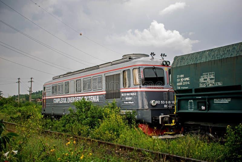Foto eingelassenes Rumänien am 19. Juni 2019 Es wird einer alten Lokomotive fotografiert, die Holzkohlenlastwagen transportiert lizenzfreie stockfotografie