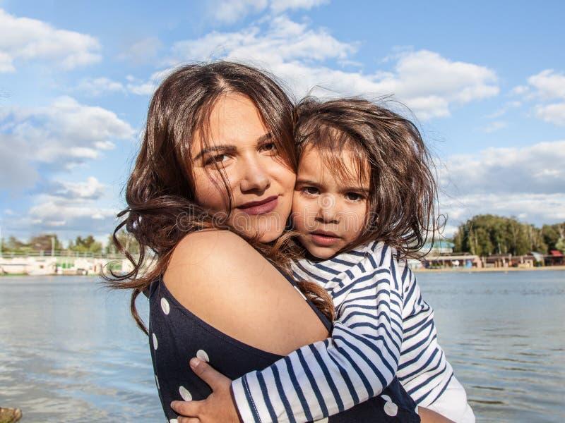 Foto emocional de una muchacha de cuatro años madre joven hermosa con un niño en naturaleza fotografía de archivo libre de regalías