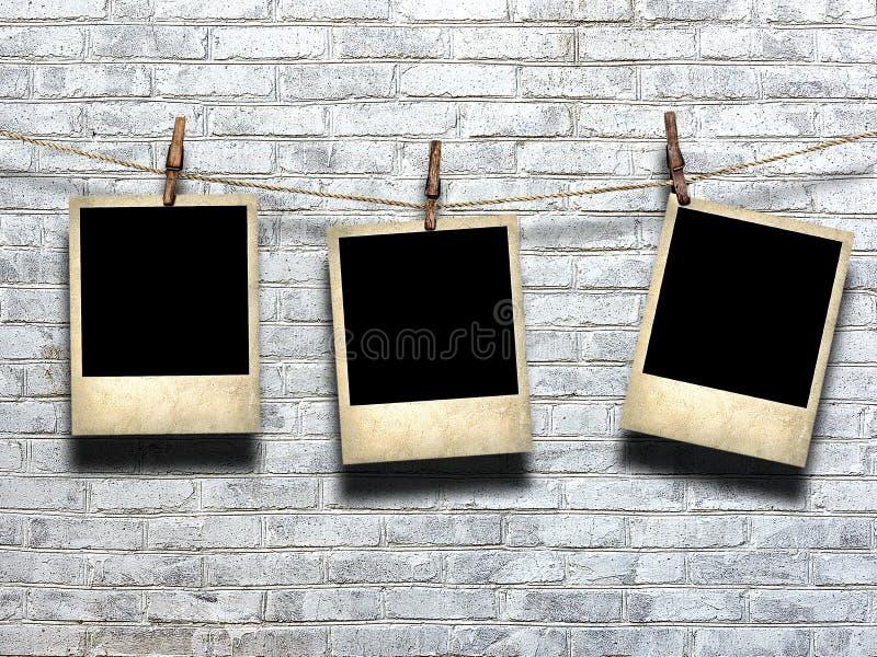 Foto en cuerda con las pinzas en un fondo de una pared de ladrillo fotografía de archivo