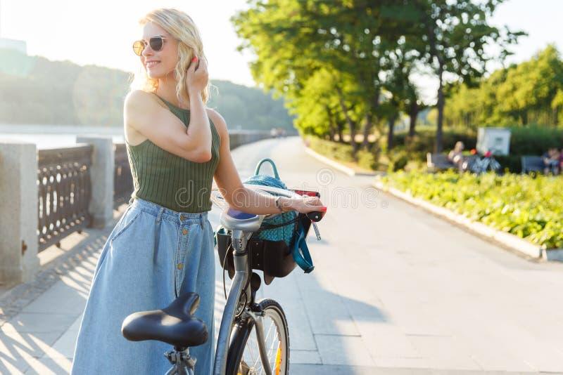 Foto en del lado de mirada rubio rizado en la situación de la falda del dril de algodón al lado de la bici en el puente en ciudad imágenes de archivo libres de regalías