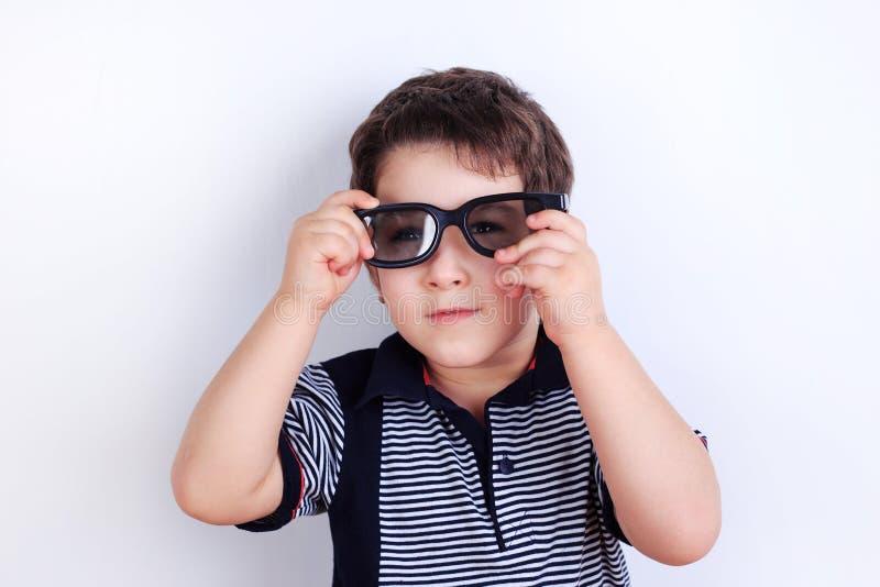 Foto engraçada do rapaz pequeno bonito que põe sobre óculos de sol, sho do estúdio imagem de stock
