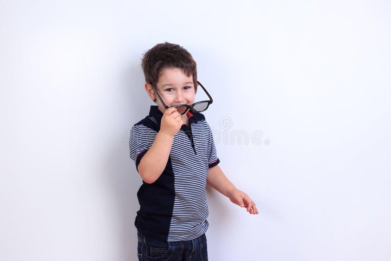 Foto engraçada do rapaz pequeno bonito que põe sobre óculos de sol, sho do estúdio fotos de stock