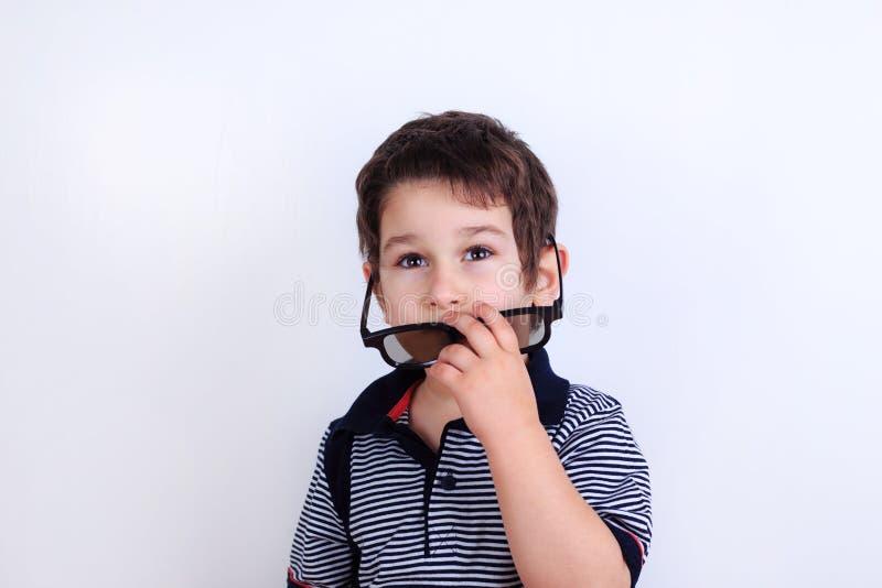 Foto engraçada do rapaz pequeno bonito que põe sobre óculos de sol, sho do estúdio fotografia de stock