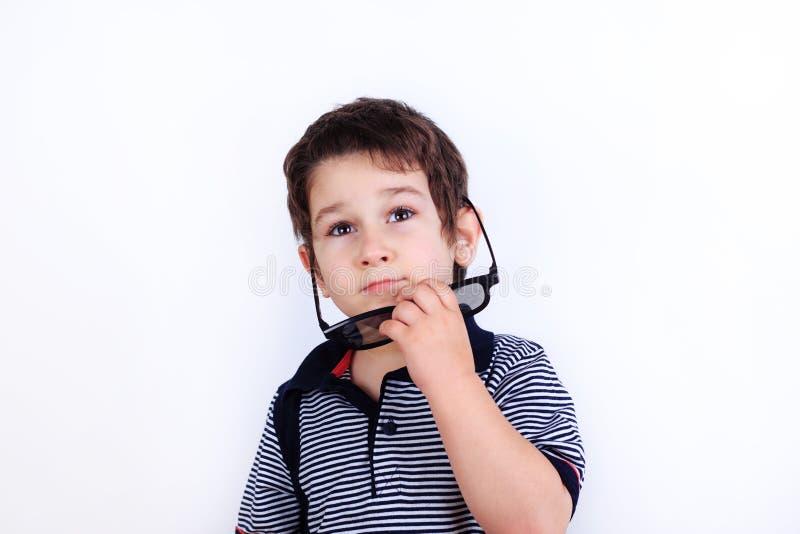 Foto engraçada do rapaz pequeno sonhador bonito que põe sobre óculos de sol, stu fotos de stock royalty free