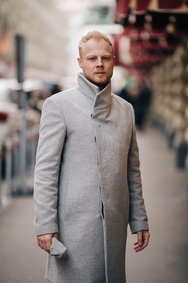 Foto entonada del hombre en capa gris que camina en ciudad fotografía de archivo libre de regalías