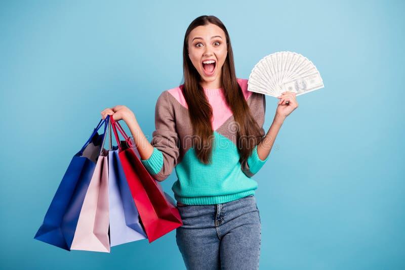 Foto erstaunten schreienden wow omg lustigen Mädchens, das einige Taschen in den Händen zeigen Stapel von amerikanischen Banknote lizenzfreies stockfoto