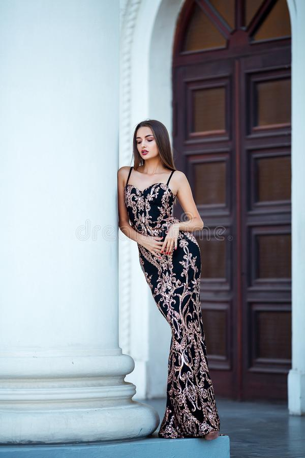 Foto exterior da forma da menina sensual bonita com cabelo escuro no vestido elegante que levanta na arquitetura antiga fotos de stock