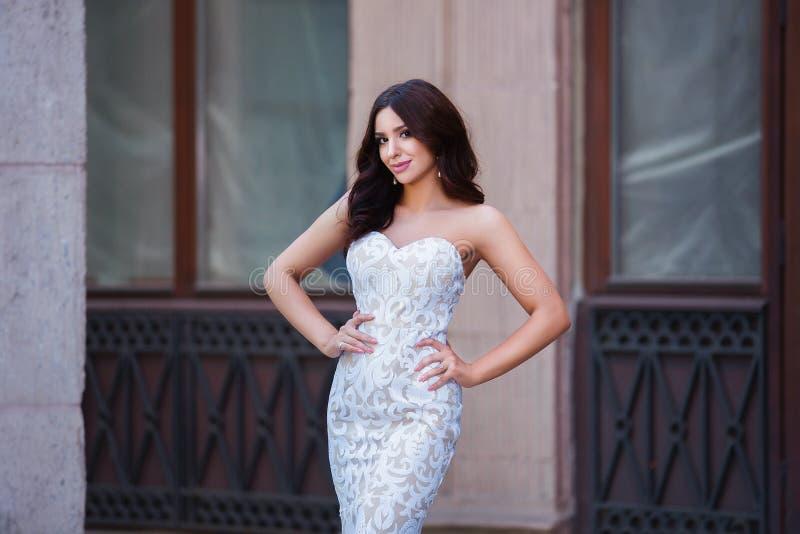 Foto exterior da forma da menina sensual bonita com cabelo escuro no vestido elegante que levanta na arquitetura antiga fotografia de stock royalty free