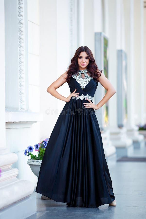 Foto exterior da forma da menina sensual bonita com cabelo escuro no vestido elegante que levanta na arquitetura antiga imagem de stock