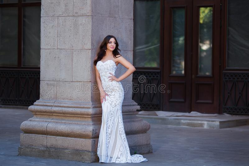Foto exterior da forma da menina sensual bonita com cabelo escuro no vestido elegante que levanta na arquitetura antiga fotografia de stock
