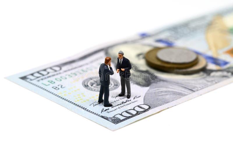 Foto för affärsmanminiatyrstatyettmakro Kontanta pengar - USA sedel och mynt royaltyfri bild
