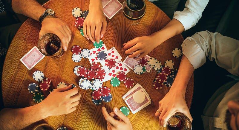 Foto för bästa sikt av vänner som sitter på trätabellen Vänner som har gyckel, medan spela brädeleken royaltyfri bild