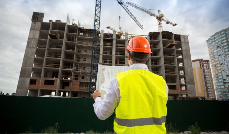 Foto för bakre sikt av den manliga arkitekten, i hardhatanseende på byggnadsplats och att se på ritningar arkivfoton