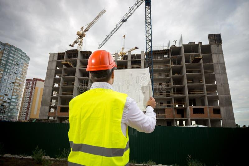 Foto för bakre sikt av den manliga konstruktionsteknikern med ritningar som kontrollerar arbete på byggnadsplats arkivfoton