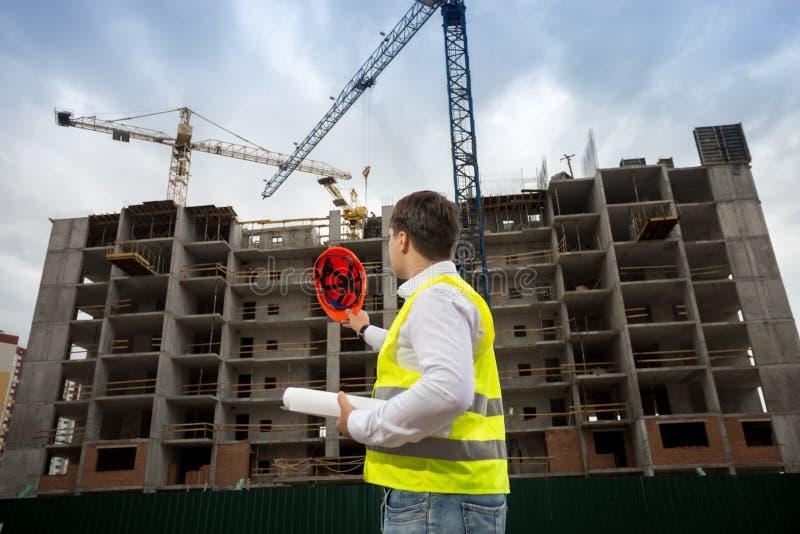 Foto för bakre sikt av den manliga konstruktionsteknikern som pekar med hardhaten på byggnadsplats arkivfoton