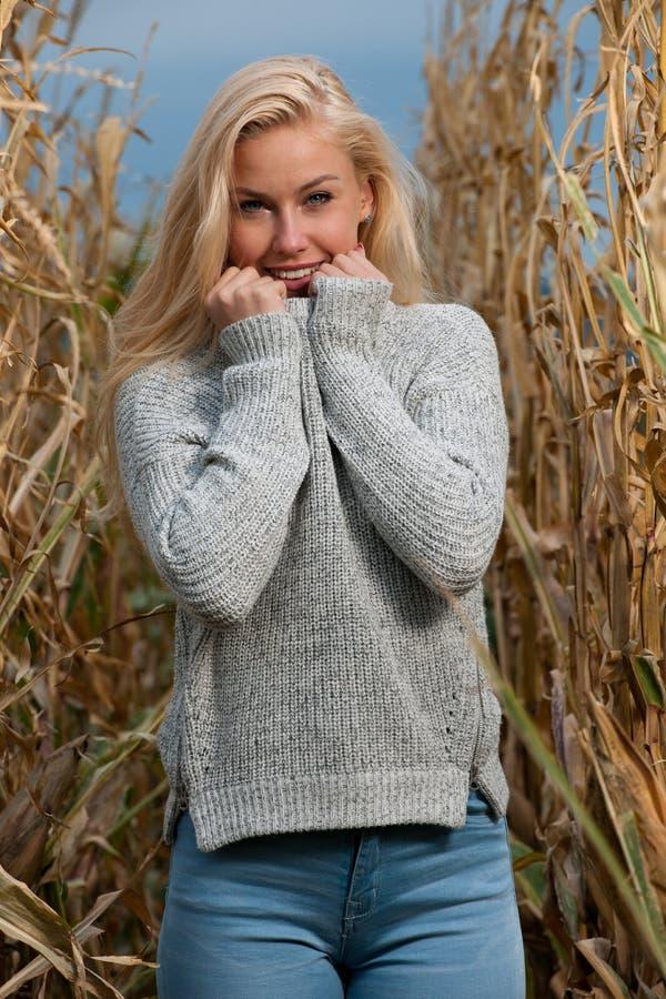 Foto för bloggstilmode av den gulliga blonda kvinnan på havrefält i sen höst arkivfoton