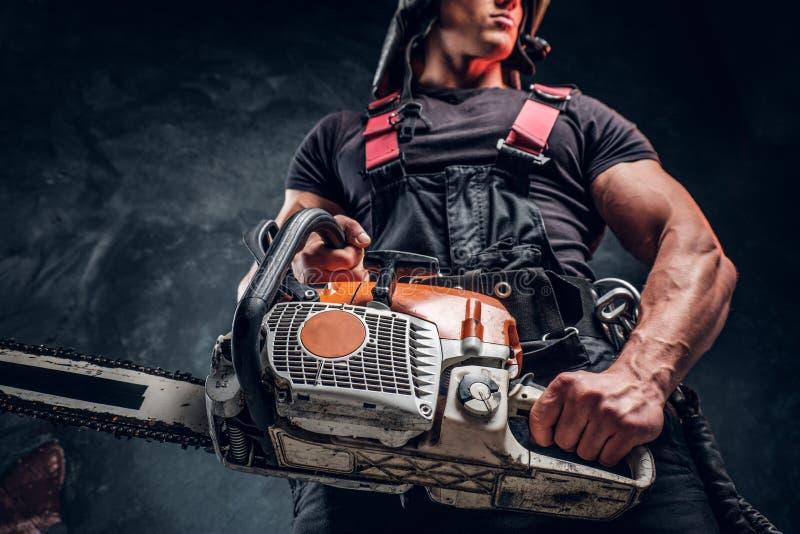 Foto för låg vinkel av en skogsarbetare med en chainsaw i en mörk studio royaltyfri foto