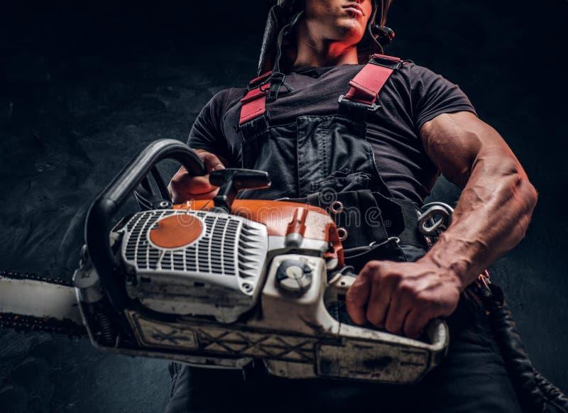 Foto för låg vinkel av en skogsarbetare med en chainsaw i en mörk studio fotografering för bildbyråer