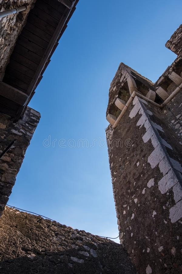 Foto för låg vinkel av slitna stenväggar av en slott med bakgrund för blå himmel royaltyfria bilder