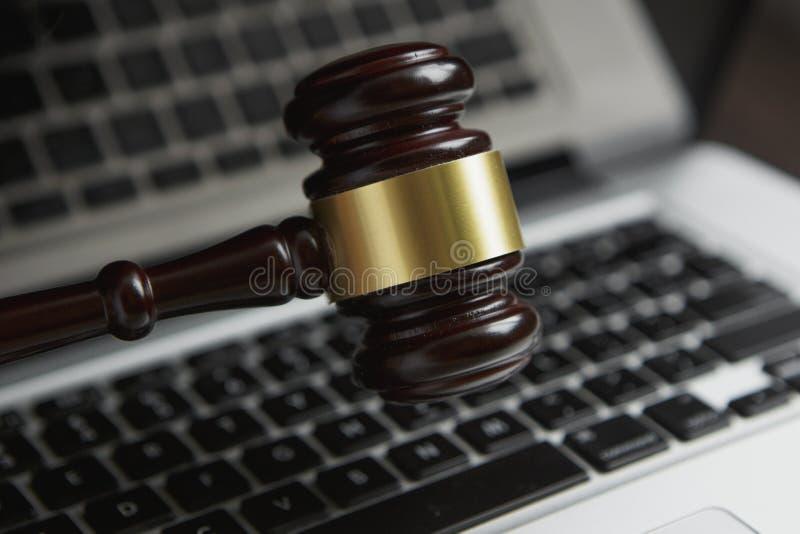 Foto för lagligt begrepp för lag av auktionsklubban på datoren med lagliga böcker i bakgrund arkivbild