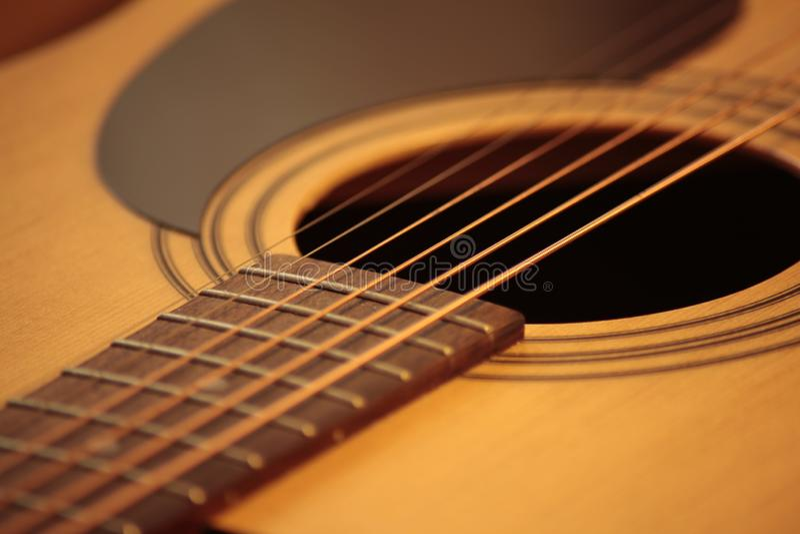Foto f?r akustisk gitarr i hemtrevliga varma signaler royaltyfria bilder