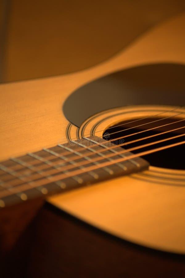 Foto f?r akustisk gitarr i hemtrevliga varma signaler royaltyfri fotografi