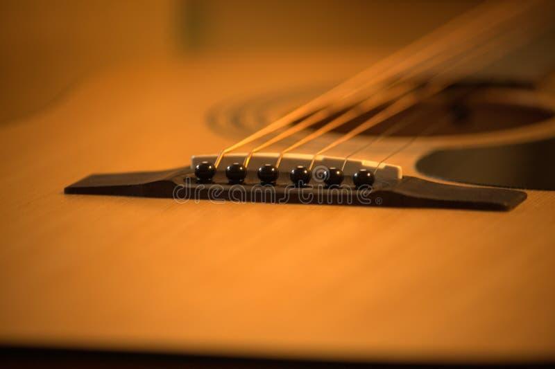 Foto f?r akustisk gitarr i hemtrevliga varma signaler arkivfoto