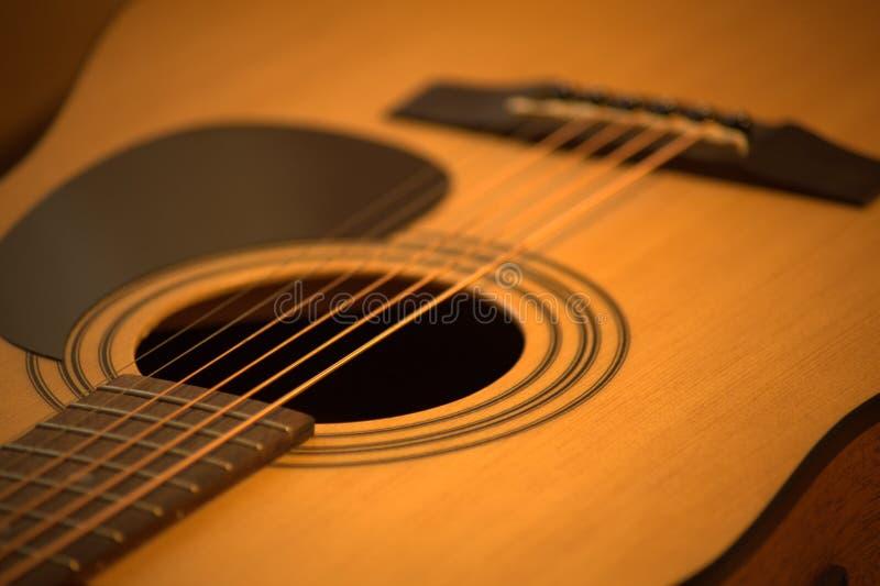 Foto f?r akustisk gitarr i hemtrevliga varma signaler arkivfoton