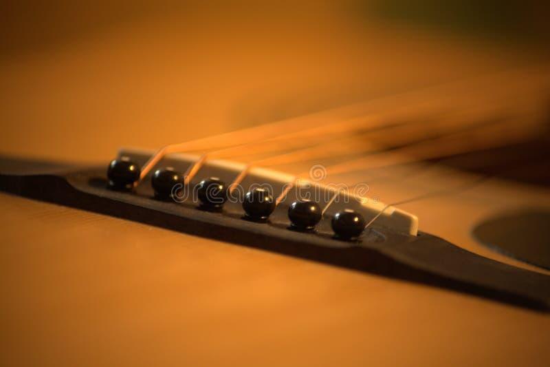 Foto f?r akustisk gitarr i hemtrevliga varma signaler arkivbilder